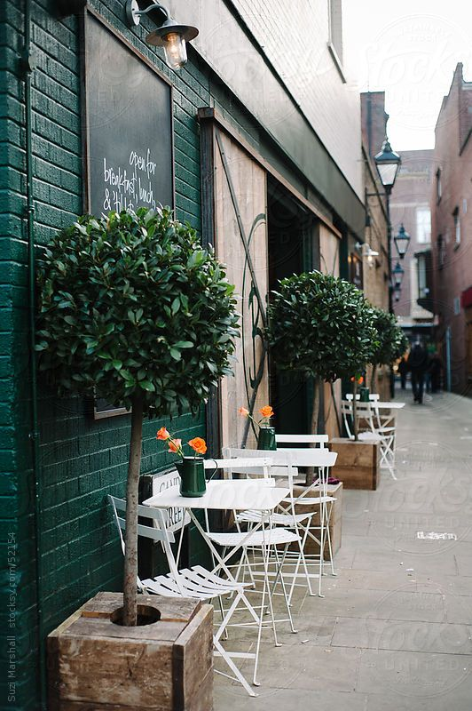 Tables and chairs in the street outside a restaurant  by Suzi Marshall