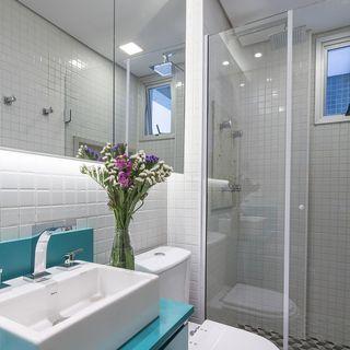 Banheiro branco com detalhes em azul e espelho amplo