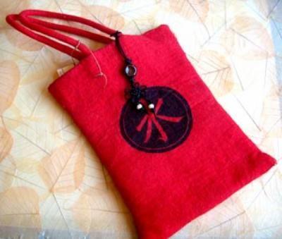 Bolso chino de fieltro hecho a mano con lana merina. Está pintado y lleva un colgante con nudos y abalorios