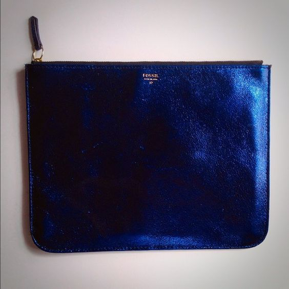 Metallic blue Fossil iPad bag Amazing metallic blue color!! I bought this for my iPad, but never ended up using it. Can be used as a cute clutch or iPad case. Has a minor scratch and mark but I couldn't capture it because of the metallic fluorescence. Not noticeable though, I was just thoroughly examining it. Fossil Bags Clutches & Wristlets