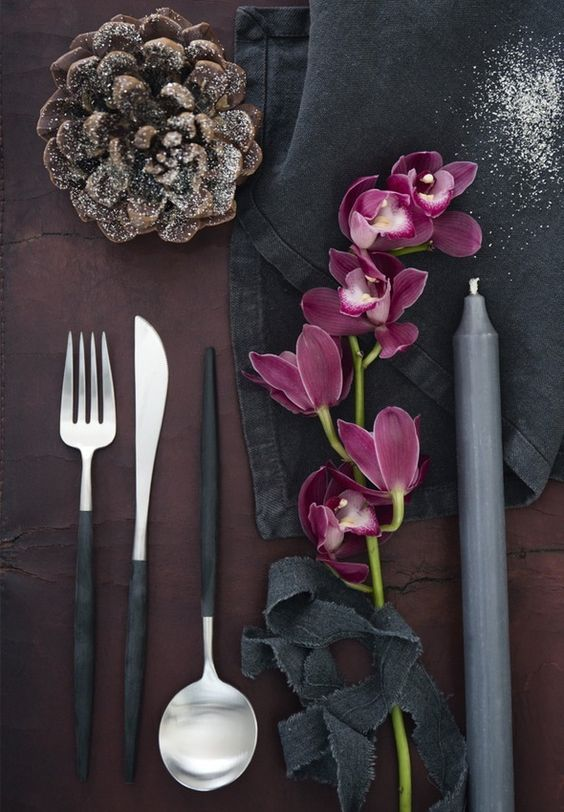 Beautiful table setting in dark tones featuring purple orchid, modern cutlery and rustic napkins.