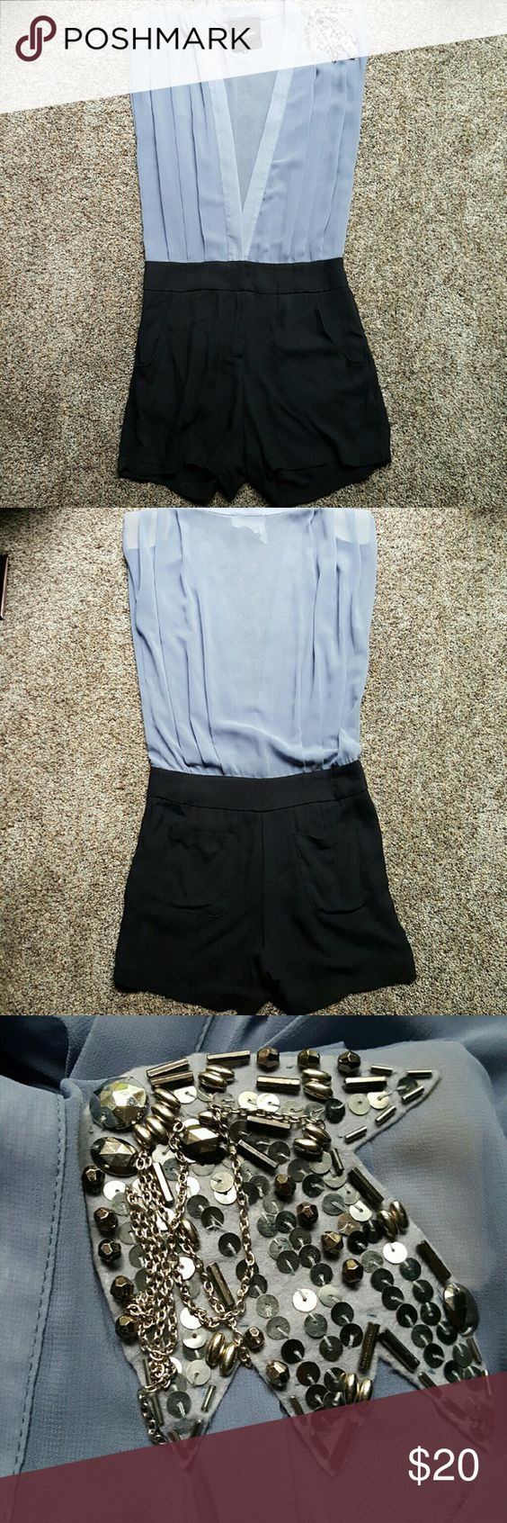 """Dressy Deep V Romper Purchased at a local boutique and worn once by my 5'7"""" cousin. It doesn't work for my shorter torso. The brand is Pepper; Size Medium. The top is a periwinkle blue, sheer material with an open deep V neck (plunges to the waist band of the shorts), small shoulder pads and embellishment on the shoulder and the bottoms are black and somewhat loose with front and back pockets. 100% Polyester and 100% Rayon contrast. 15.5"""" across (waist); 10"""" rise to zipper; 12.5"""" rise to…"""