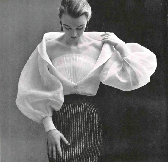 mirnah:  Hubert de Givenchy's white organdy blouse with wide sleeves, deep décoletté is crossed by a modesty fan pleat. Photographed by Phiippe Pottier, 1952.: