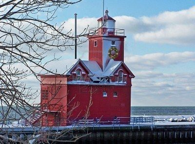 Holiday wreath on a red lighthouse in the winter.