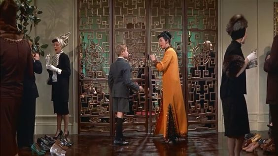 Auntie Mame and Patrick prepare to enter the dining area to sample octopus and caviar: