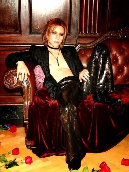 黒いジャケットを着て赤いソファーに座っているXJAPAN・YOSHIKIの画像