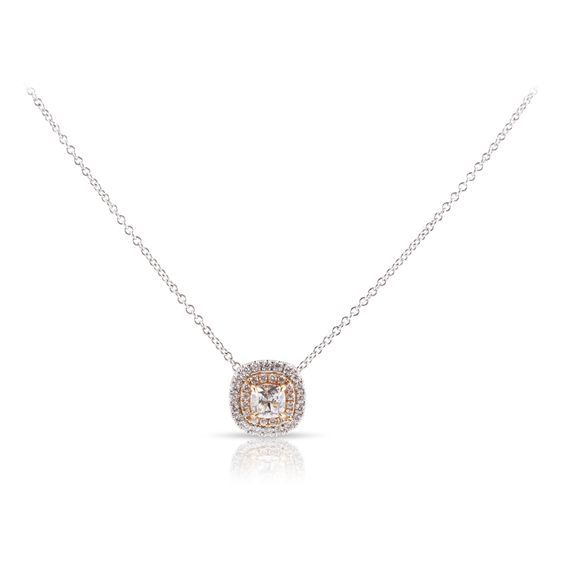 A responsibly sourced Forevermark cushion cut center diamond is surrounded by a rose and white gold two-tone diamond double halo. See this pendant necklace and more at rfmoeller.com.