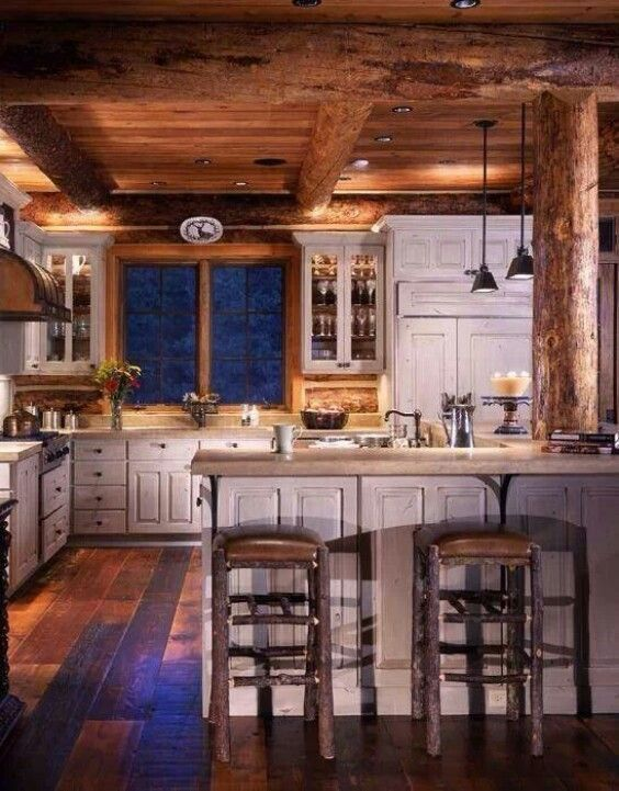 Log cabin kitchen I love the distressed white cabinets They make