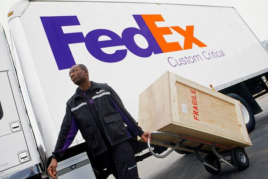 FedEx drivers grab packages off a conveyor belt as they load their - fedex jobs