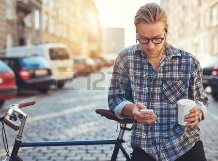 Outdoor portrait of modern young man with mobile phone in the street sitting on bike Stock Photo:
