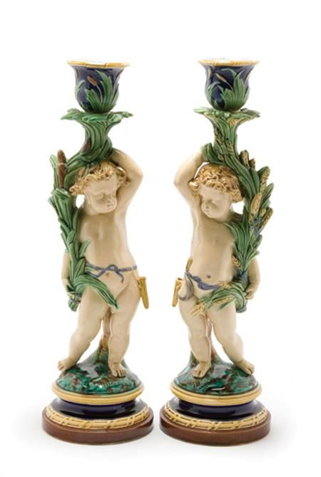 Pair of Minton Majolica Figural Candlesticks  Each in the form of a putto standing beside a tree trunk holding a cornucopia formed from cattails or wheat sheaves, on a stepped circular base,
