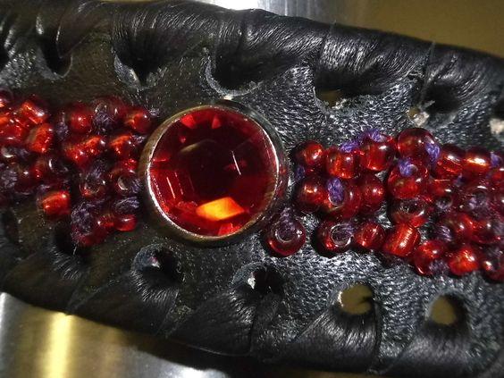 Schwarzes Lederarmband............mit RubinrotenGlasperlen bestickt und roten Strass-Steinen.Hand umnäht