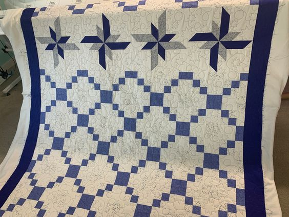 The little tiny blue spots in this quilt reminded me of stars so we quilted stars. I love the big blue pinwheel type blocks that make this quilt stand out. The client wanted the stitching to pop so we used blue thread.