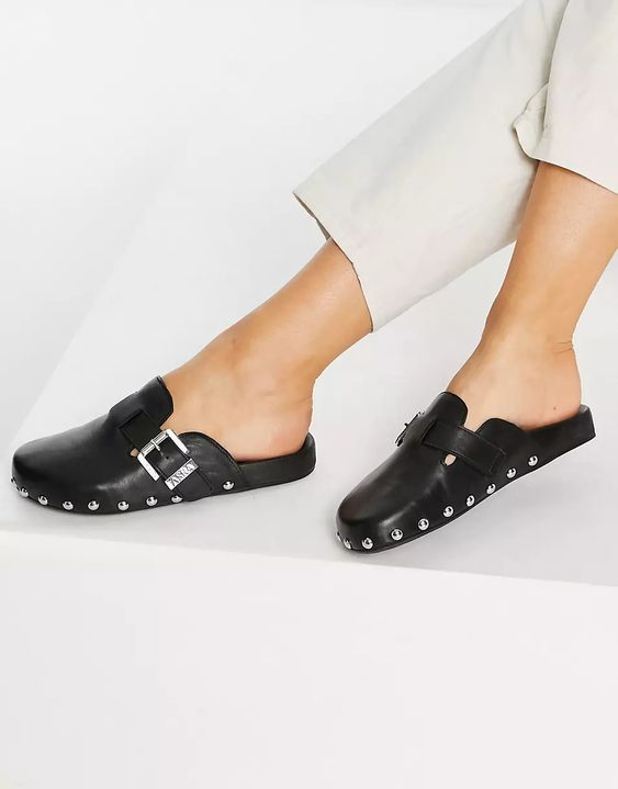Woman's feet wearing studded clogs in black leather and silver buckles from ASRA London