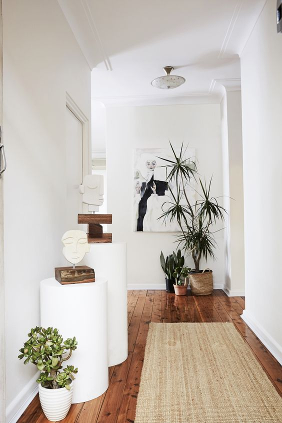 "A ""minimal '70s vibe"" is created in the entrance of this home with the use of natural textures and indoor plants against a clean white backdrop. Photography: Kristina Soljo 
