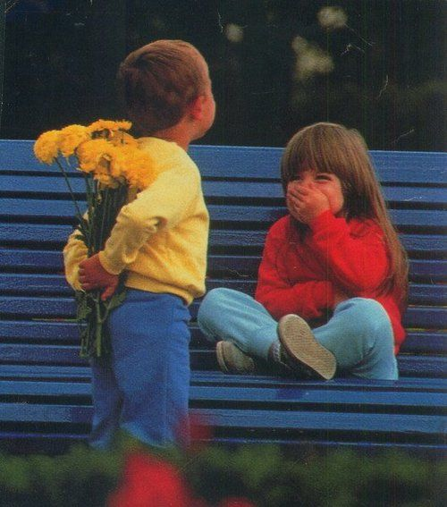 Petit garçon qui offre des fleurs à une petite fille / Little boy giving flowers to a little girl