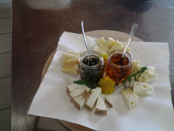 Tagliere di formaggi con boccioli di tarassaco sottaceto e sciroppo di fiori di tarassaco