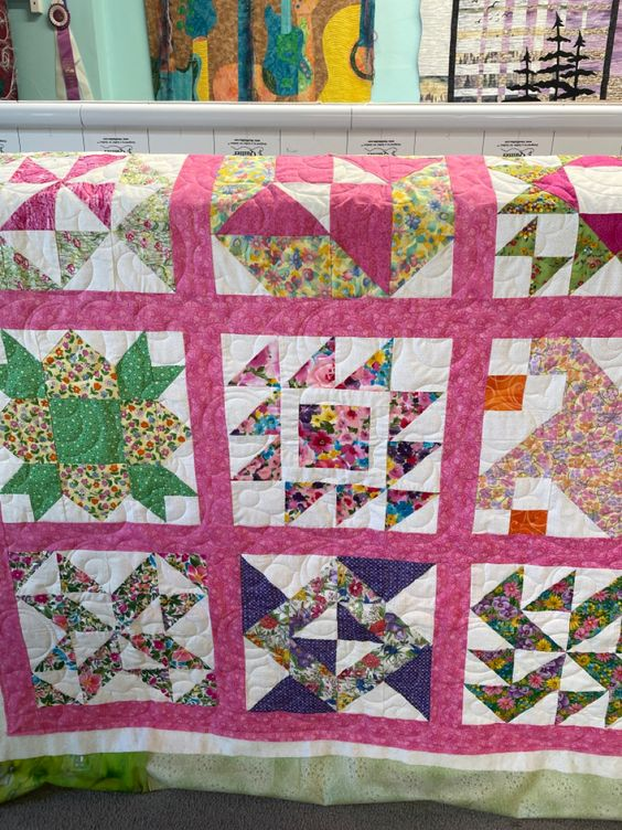 This is a charity quilt for the Linus Project. I actually piced it 17 years ago. I decided it was better used than sitting in my closet! Quilted flower swirl from Deb Geissler designs. #quilts #longarmquilting #linusproject #charity #quilting #flowers #quiltblockideas #babyquilt