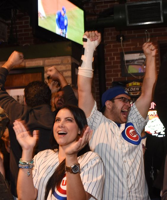 Debbie Roumeliotis and Chris Nemea of Chicago celebrate after the Cubs turned a inning-ending double play against the Pirates on Wednesday night. The fans were watching the National League wild-card game at Murphy's Bleachers, across the street from Wrigley Field, in Chicago.