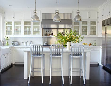 All-White Kitchen with Black Floor    White scullery-type cabinets mingle with glossy white subway tiles, marble countertops, and stainless steel appliances to create a pristine appearance in this light and airy room. Below, an oak floor stained ebony creates a dramatic contrast.