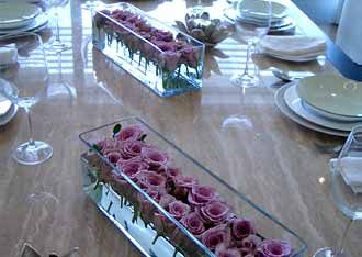 Modern table settings of low glass tank vases and rose heads