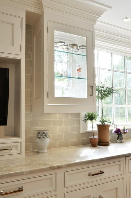 Plenty of light makes sure that these quartzite countertops shine. They also pair great with white cupboards and the complimenting backsplash.