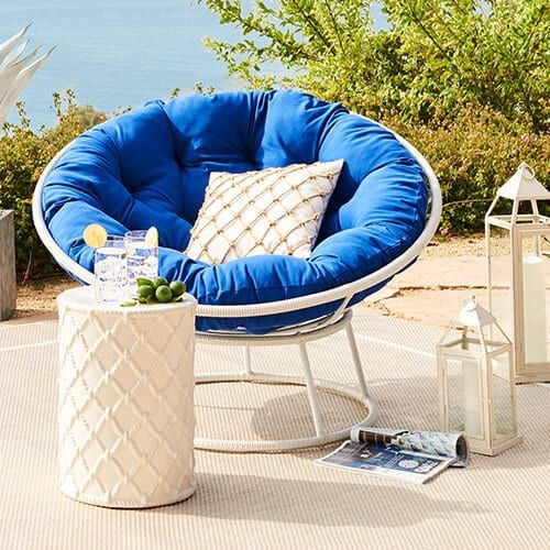 Blue Papasan Cushion With White Colored Basket In An Outdoor