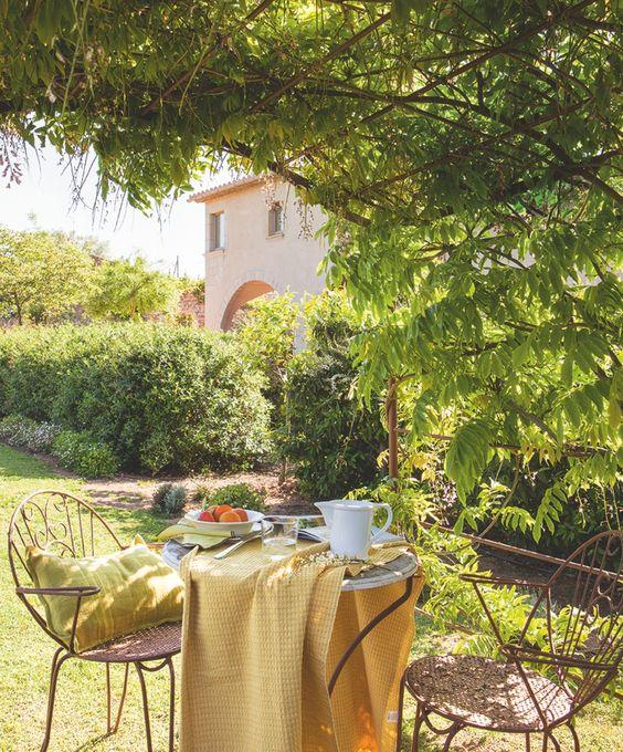 BAJO LA PÉRGOLA Una glicinia viste la pérgola y protege del sol este rincón. Cojín de La Maison y mantel amarillo de Calma House.
