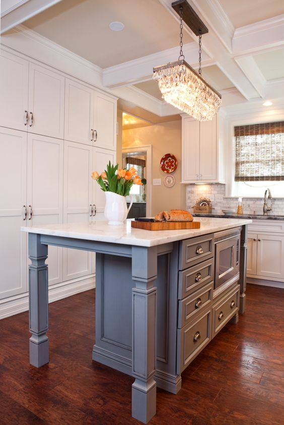 White kitchen with gray island and marble countertop designed by Karr Bick Kitchen & Bath
