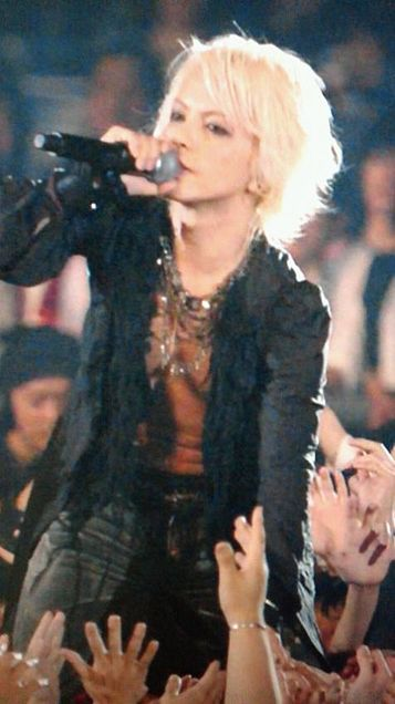 ファンに囲まれて歌っている金髪スタイルのL'Arc〜en〜Ciel・hydeの画像