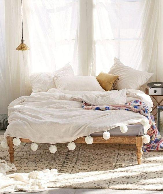 chambre bohème avec couverture blanche décorée de pompons, tapis beige à motifs noirs et un grand rideau blanc et semi-transparent