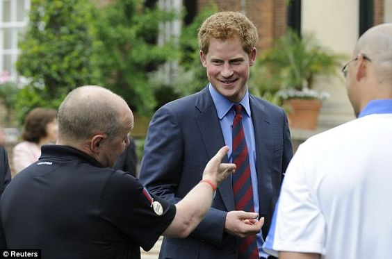 Britain's Prince Harry (Centre) smiles as he greets wounded UK service members at the British Embassy in Washington DC.