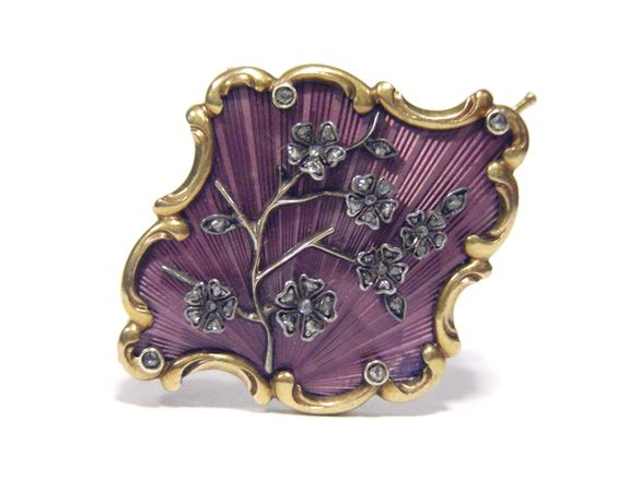 An enamelled and jewelled cherry blossom brooch by Carl Fabergé, enamelled translucent mauve over a sunburst ground and mounted with diamond set cherry blossom, within a yellow gold rocaille border further highlighted with diamonds. Fabergé Moscow, pre 1896, inventory number 14039 .