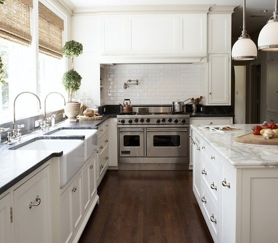 White cabinetry, windows, walnut floor and marble and subway tile add interest to this classic white kitchen