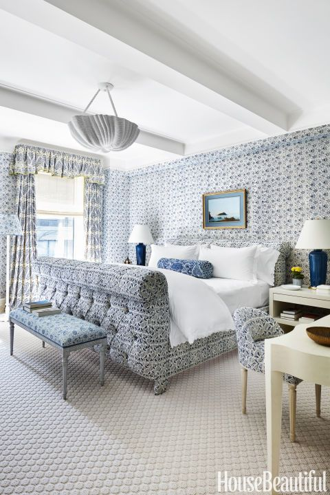 """Markham Roberts: In the master bedroom, a tufted sleigh bed is a nod to the iconic designer Syrie Maugham. The bed and curtains are in prints by Lake August, and the walls are covered in an Alamwar pattern, all from Studio Four NYC. """"It sounds over-the-top, but layers of blue-and-white patterns can actually be coherent and calming,"""" Roberts says."""