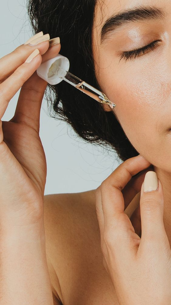 Young woman applying serum on her face | premium image by rawpixel.com / McKinsey