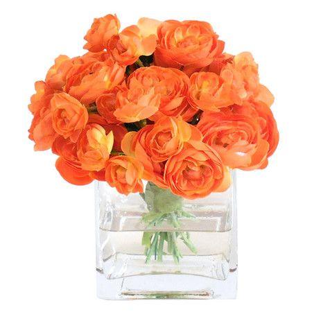 Faux ranunculus arrangement in a glass vase.     Product: Faux floral arrangementConstruction Material: Glass...