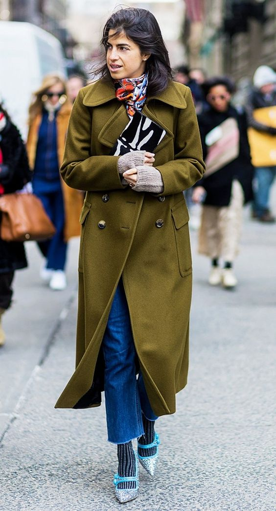 An olive green coat is paired with a printed scarf, patterned clutch, blue jeans, gray socks, and sparkly pointed-toe pumps