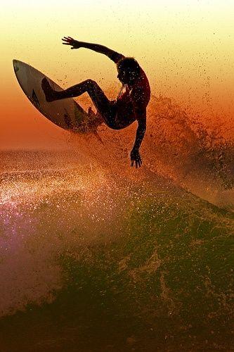 夕焼けと飛ぶ男性サーファー
