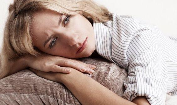 Depression: Frau mit traurigem Gesichtsausdruck legt ihren Kopf auf ein Kissen