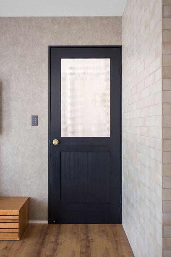 ブラックのドアとグレージュのタイルやクロスがリビングのアクセントに
