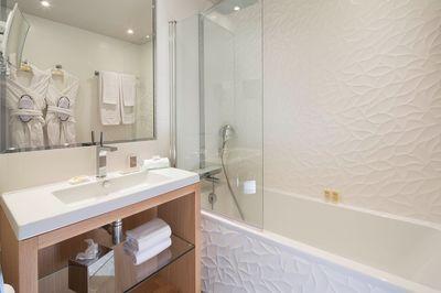 Design, cette salle de bains blanche avec faience matiérée, meuble de toilettes en bois pour la chaleur