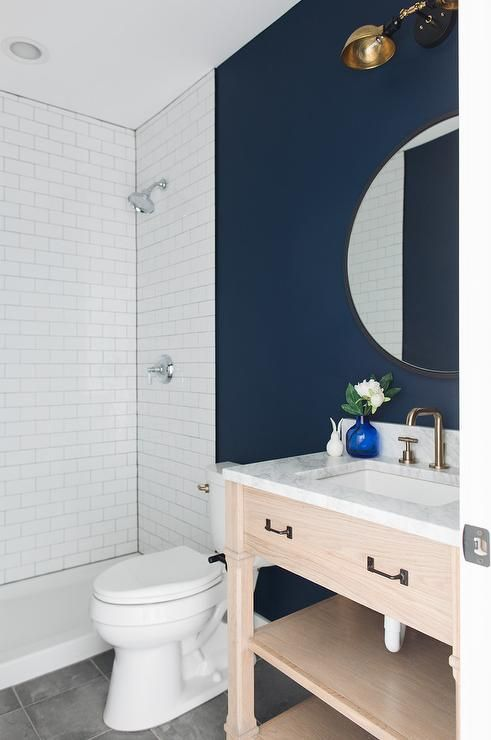 Navy Blue And White Powder Room Features A Light Oak Single Washstand Fitted With A Shelf And A Satin Nickel Bathroom Wall Colors Blue Bathroom Blue Room Paint