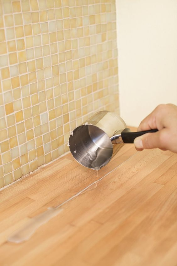 Use melted canning wax to fill cracks or separations in wood countertops and scrape off excess before sealing with a finish.
