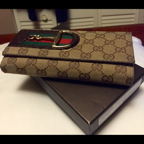 Gucci Canvas Hasler Continental Wallet Brown GG canvas bi-fold continental style wallet with textured leather, classic signature red/green trim and gold horsebit hardware. Outer flap pocket with snap closure. 7 card slots and 2 bill pockets. Good condition. Corners and hardware show signs of normal wear. Some wear noted on interior leather. Comes with box. Gucci Bags Wallets