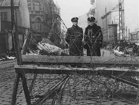 """Os nazistas forçaram alguns judeus a servirem como """"guardas"""" de seus próprios irmãos. Nesta foto pode-se ver """"policiais"""" judeus em uma barricada na entrada do Gueto de Varsóvia. Polônia. Fevereiro de 1941."""