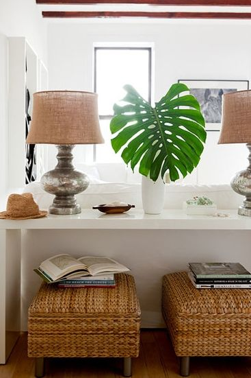 Little ottomans under a console table could make perfect extra seating that is out of the way or little work area behind couch.: