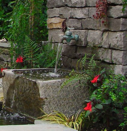 fun faucet to large millstone or solid block of stone into a basin or linear pool and recirculates back