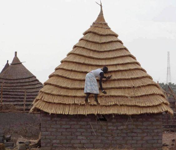 África - mulher africana dando os últimos retoques no telhado de palha de sua casa...que capricho!