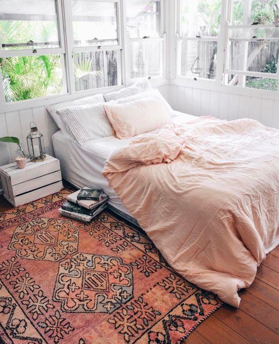 Un chambre à l'esprit bohème avec ce grand tapis et sa table de chevet de récup'